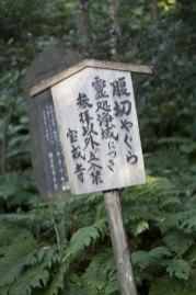 管理する宝戒寺による立て札。「霊処浄域につき、参拝以外の立入禁止」とあります。奥の石碑とともに斜めに傾いていました。