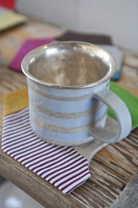 瑞々しく絵付けされ、内側に銀が塗られた陶器のマグカップ(3,990円)は中囿義光さんの作。相性抜群のコースター(945円)は布作家hikiひきさんのもの。