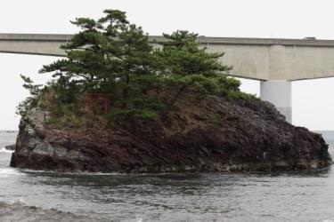 岩海岸の海岸線近くの海上にある大きな岩。鳥居が建てられています。