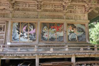 国上寺、本堂(阿弥陀堂)の絵巻。東の面「龍乗遊戯之絵巻」 「中国の五行思想では龍(厳密には青龍)は東を意味し、中国風水では家の東に龍を飾ると運気が上がるとされています。国上寺の永遠の繁栄を祈りつつ、龍に乗って遊ぶ偉人たちを空想して描きました。まだ子どもの酒呑童子は大股を開いて大はしゃぎ。同じく弁慶は、はしゃぐ酒呑童子を落ちないように支えています。一方、年齢を重ねている良寛はは泰然自若、謙信と義経はそれぞれが一流の武将、龍の上だろうが互いの剣を交えずにいられません。と、偉人たちそれぞれの性格が垣間見えるようにしています」(木村了子)