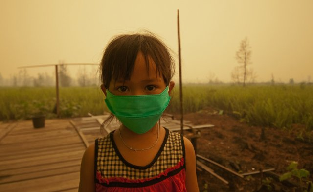 Child wearing masks due to the toxic smoke from peat land fires