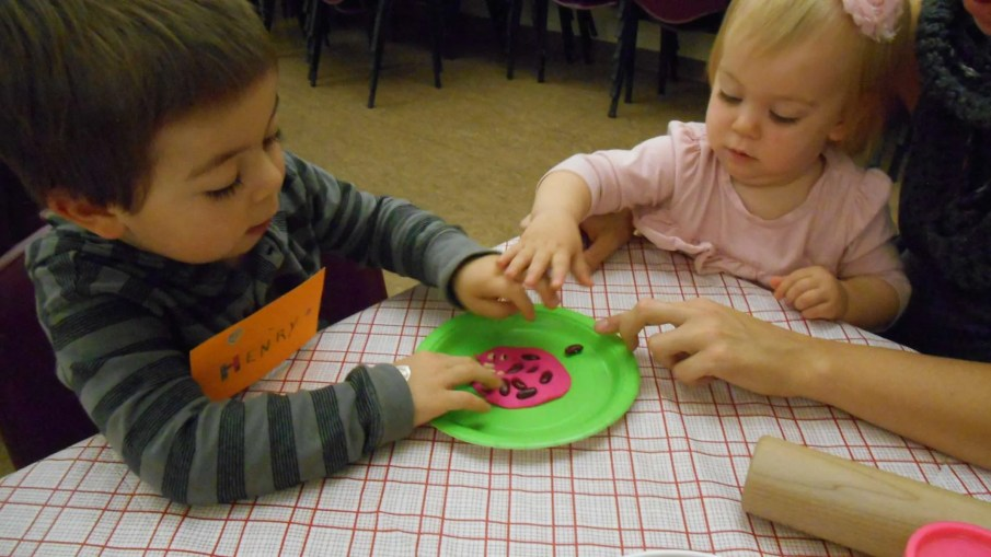 Siblings creating a seed mandala.