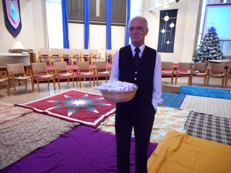 """Ian McLean, KUCs leader of """"Aboriginal Relations""""ministry at KUC, with the """"scrolls of history"""" and blankets representing the territories/lands of First Nations peoples."""