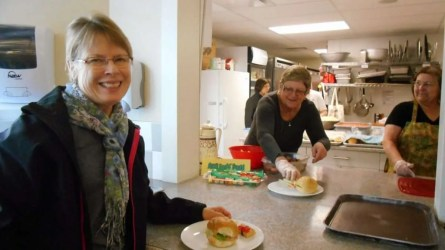A happy lunch guest (Ann D) is served her lunch by Francelyn.
