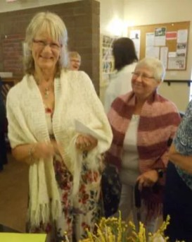 Gloria and Heather, both with Muriel-created shawls, prepare to sign the card.