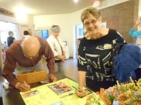 Chuck, and Judy with a Muriel-created shawl, sign the card.
