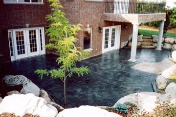 Stained concrete patio with boulder wall