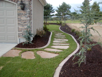 Stone path in grass with garden beds