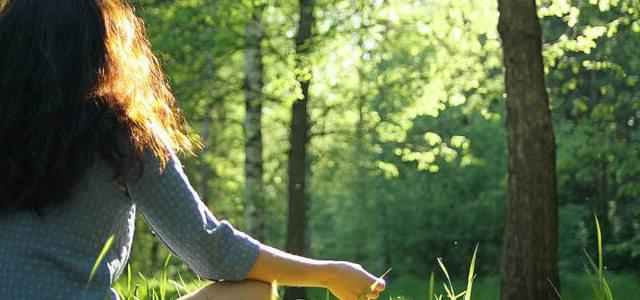 Eine Frau in einem Kleid meditiert mit einem Baum in einem Wald