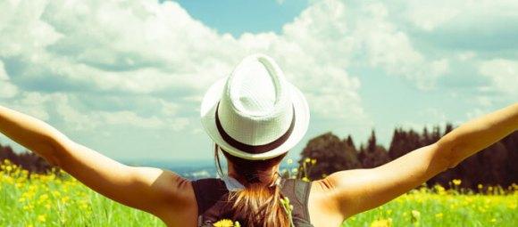 Eine Frau öffnet ihre Arme und blickt zum Himmel