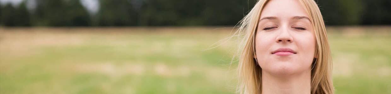 Eine bjunge blonde Frau macht meditatives Yoga in der Natur