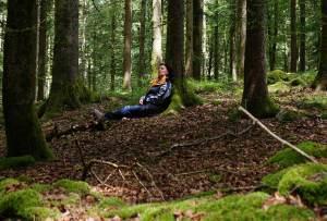 Eine reife Frau entspannt an einem Baum mitten im Wald
