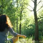 Eine Frau in einem hellblauen Kleid übt sich in der Natur in Achtsamkeit