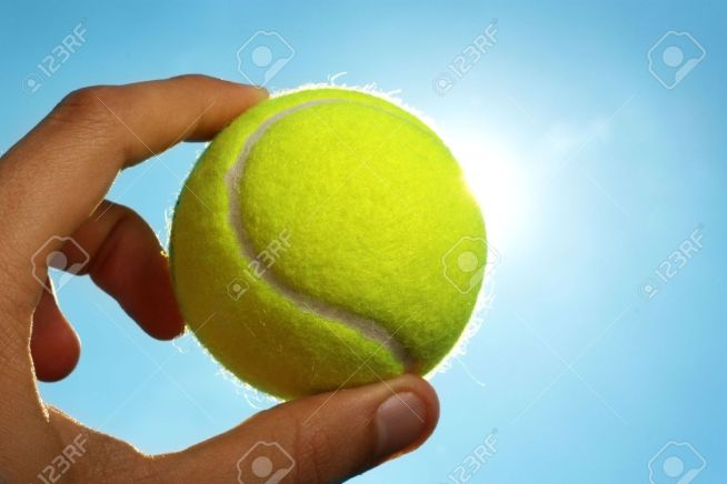 5391345-A-man-s-hand-holding-a-tennis-ball-up-to-a-blue-sky-with-the-sun-behind-it--Stock-Photo