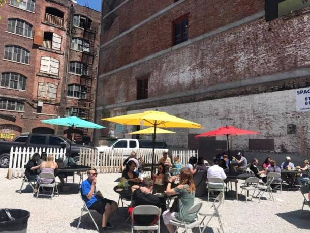 West Bottoms Historic District - several people sitting outside at patio tables enjoying snacks and shopping