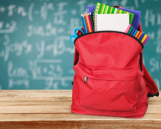 Back to school - backpack filled with school supplies sitting in front of a chalkboard