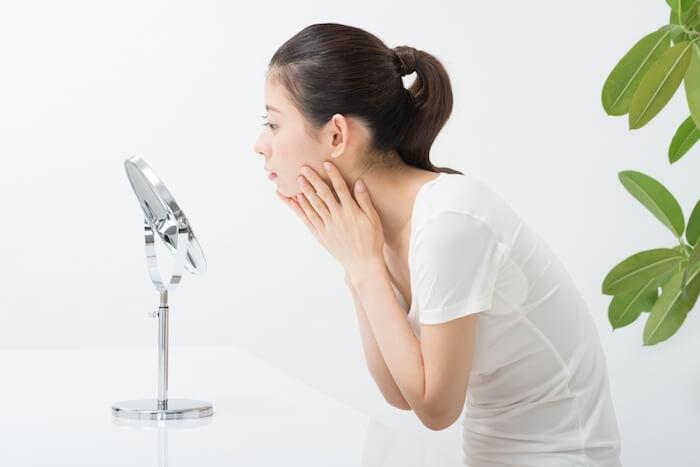 鏡で肌の状態を確認している女性の画像