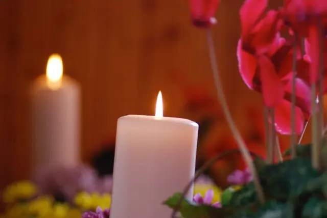 Candles amid flowers
