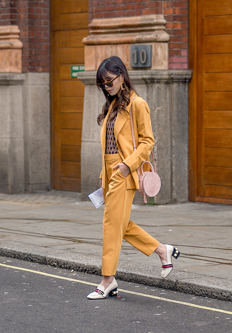 Street Style during day two of London Fashion Week AW 2019. Image shows fashion blogger Kim Bouy Tang wearing a mustard coloursuit with glasses and Gucci shoes.