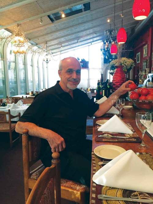 Chef Reza Azeri sits at the bar top of his restaurant Baci Bistro located in Kailua. – Kristen Kumakura
