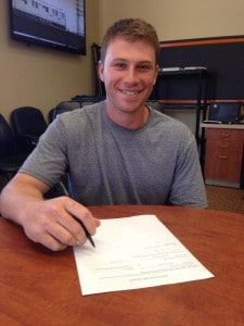 Adam Sonabend signs his contract