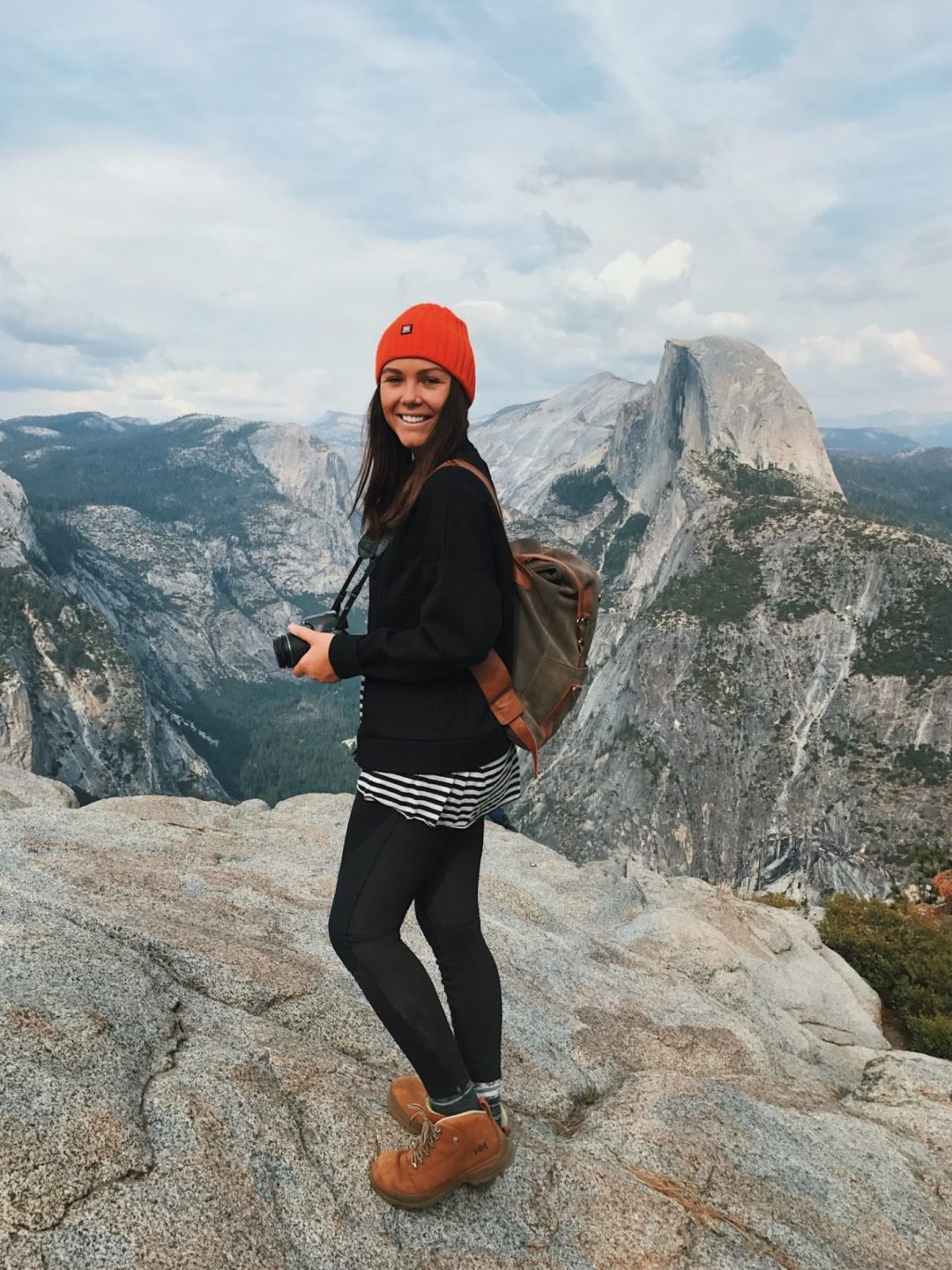 A girl in a red beanie and hiking boots stands on rock at Half Dome in Yosemite National Park