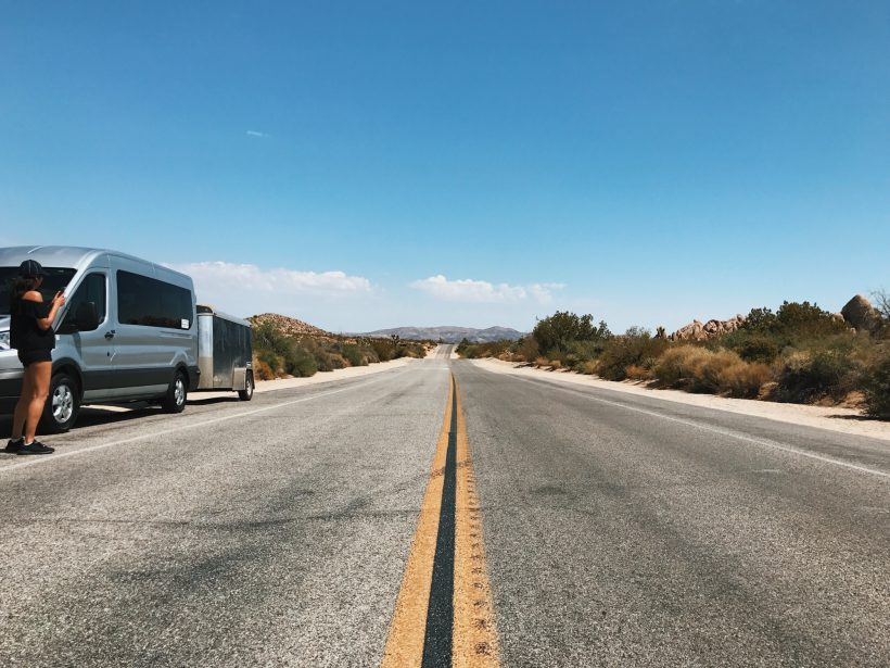 A girl stands next to a silver van parked on the side of a lonely and empty desert road.