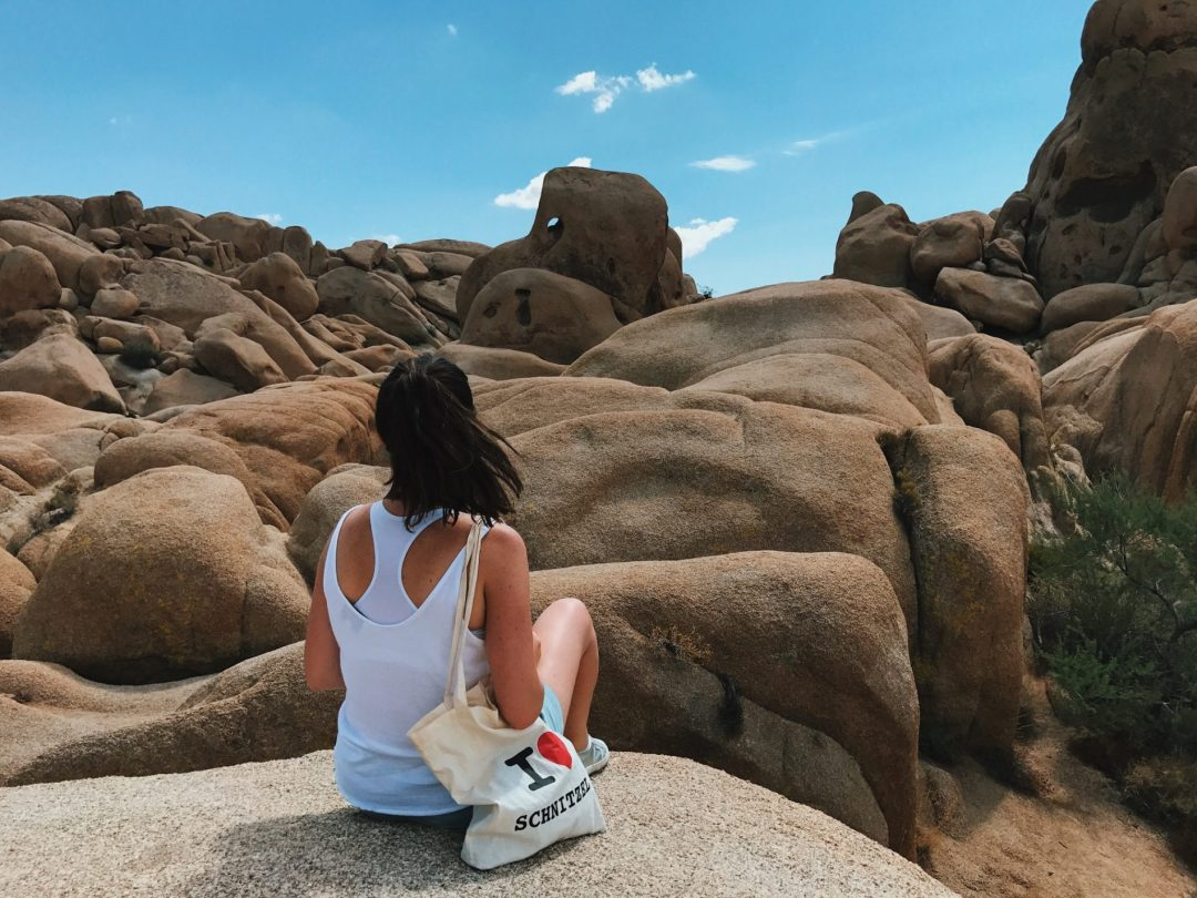 A girl sits in the desert on top of hundreds of huge boulders