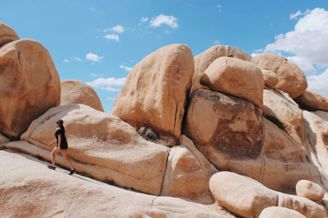 A girl in a black jumpsuit and cap is walking along some rocks in the desert. The rocks are ten times bigger than she is.