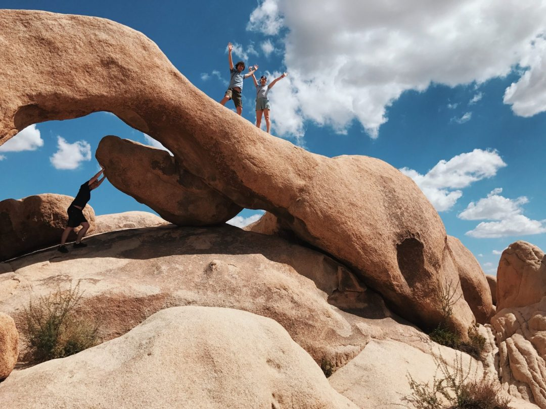 Three people standing under a huge arched rock in the desert and wave at the camera.
