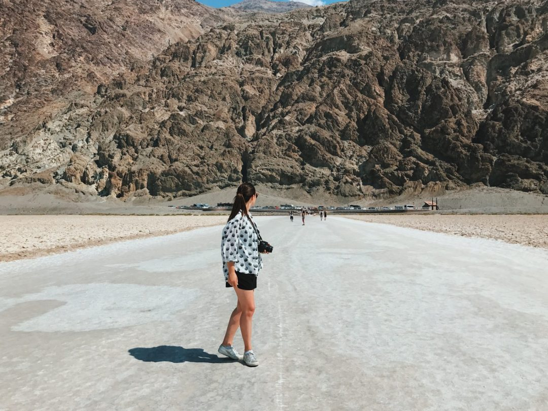 A girl stands on white salt flats