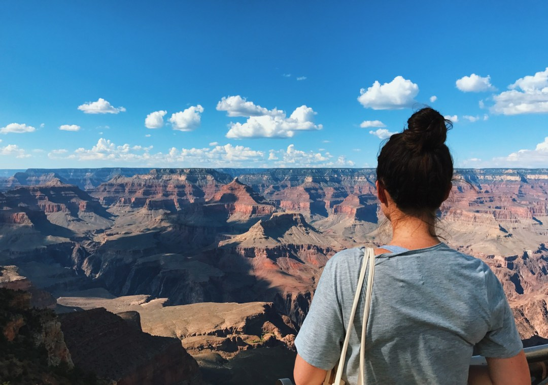 A girl standing at a lookout point at the Grand Canyon you can see the entire valley with strange rock formations and variations of red rock as far as the eye can see.