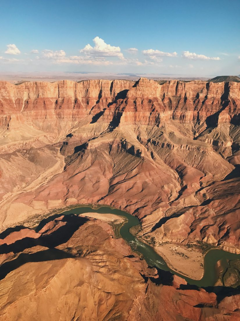 An aerial view of the Grand Canyon with the colorado river down the bottom. The rock is red and jagged and the sky is blue.