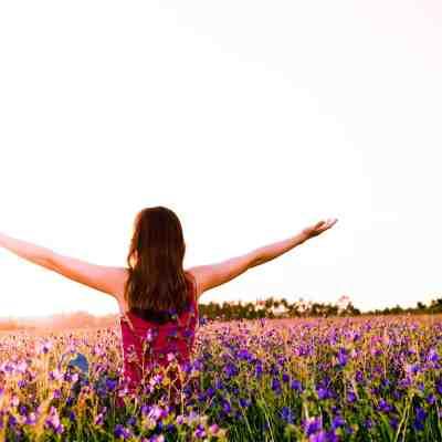 Free girl enjoying the nature on a beautiful flowery field