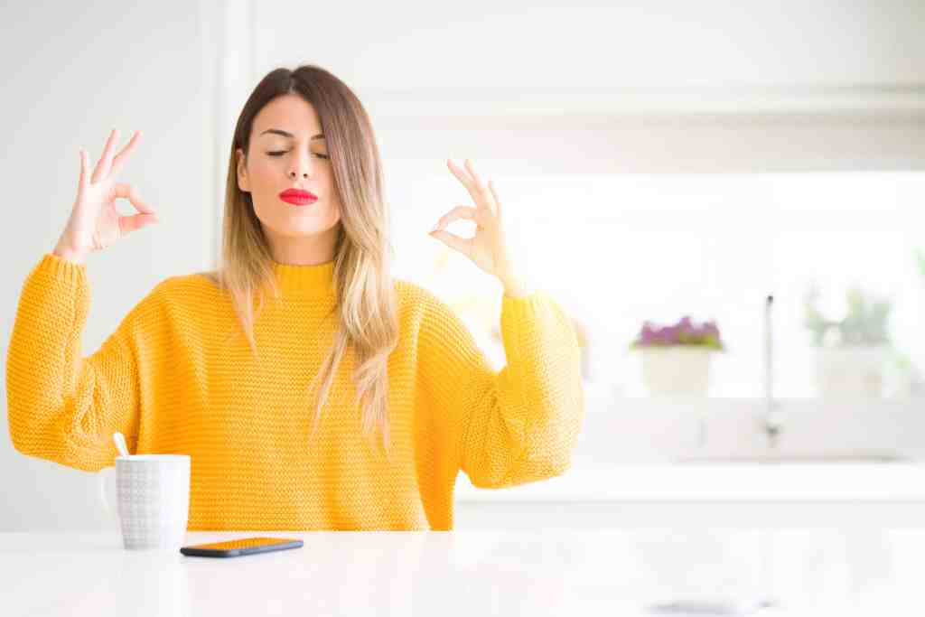 Young beautiful woman at home who is nervous for work and relaxes by smiling with eyes closed doing meditation gesture with fingers.