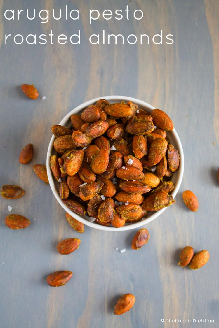 Arugula pesto roasted almonds make for a savory salty snack that's perfect for entertaining or packing with you for on-the-go. | @TheFoodieDietitian