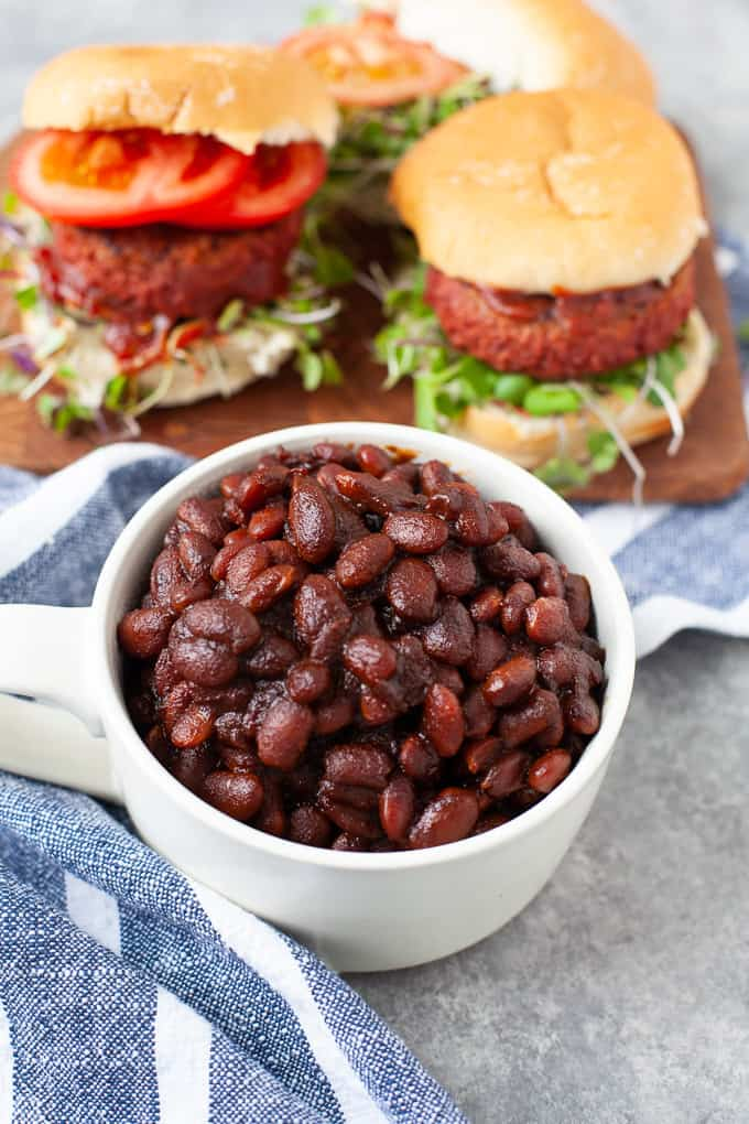 cup of baked beans served with burgers