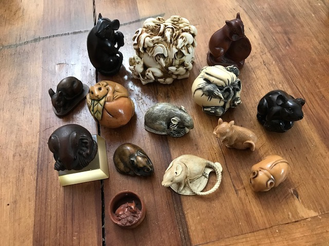14 small carvings of rats and mice on a wooden table.