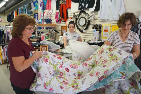 Andrea helps me fold a quilt I seleted.