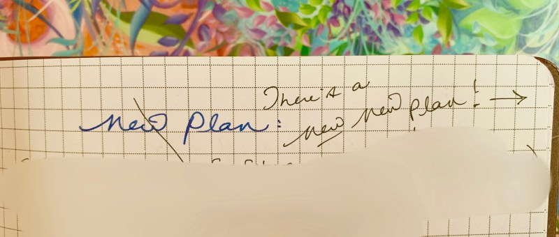 """notebook page with """"new plan"""" crossed out and """"new new plan"""" written"""
