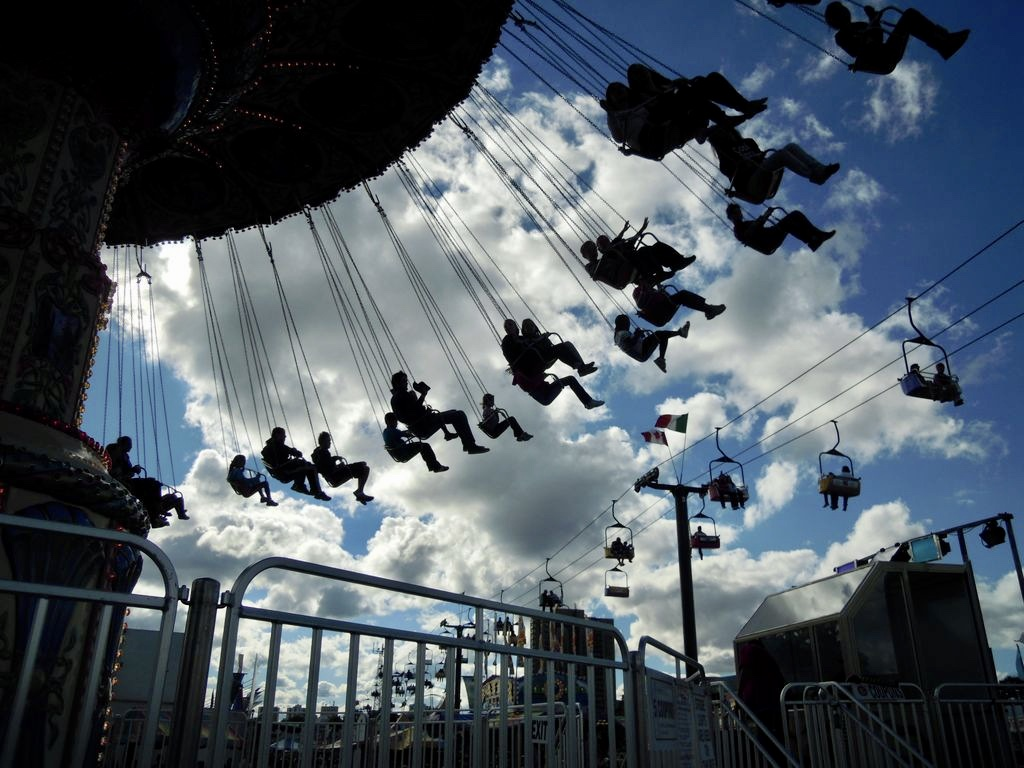 people in a swinging carnival ride against a sky with clouds