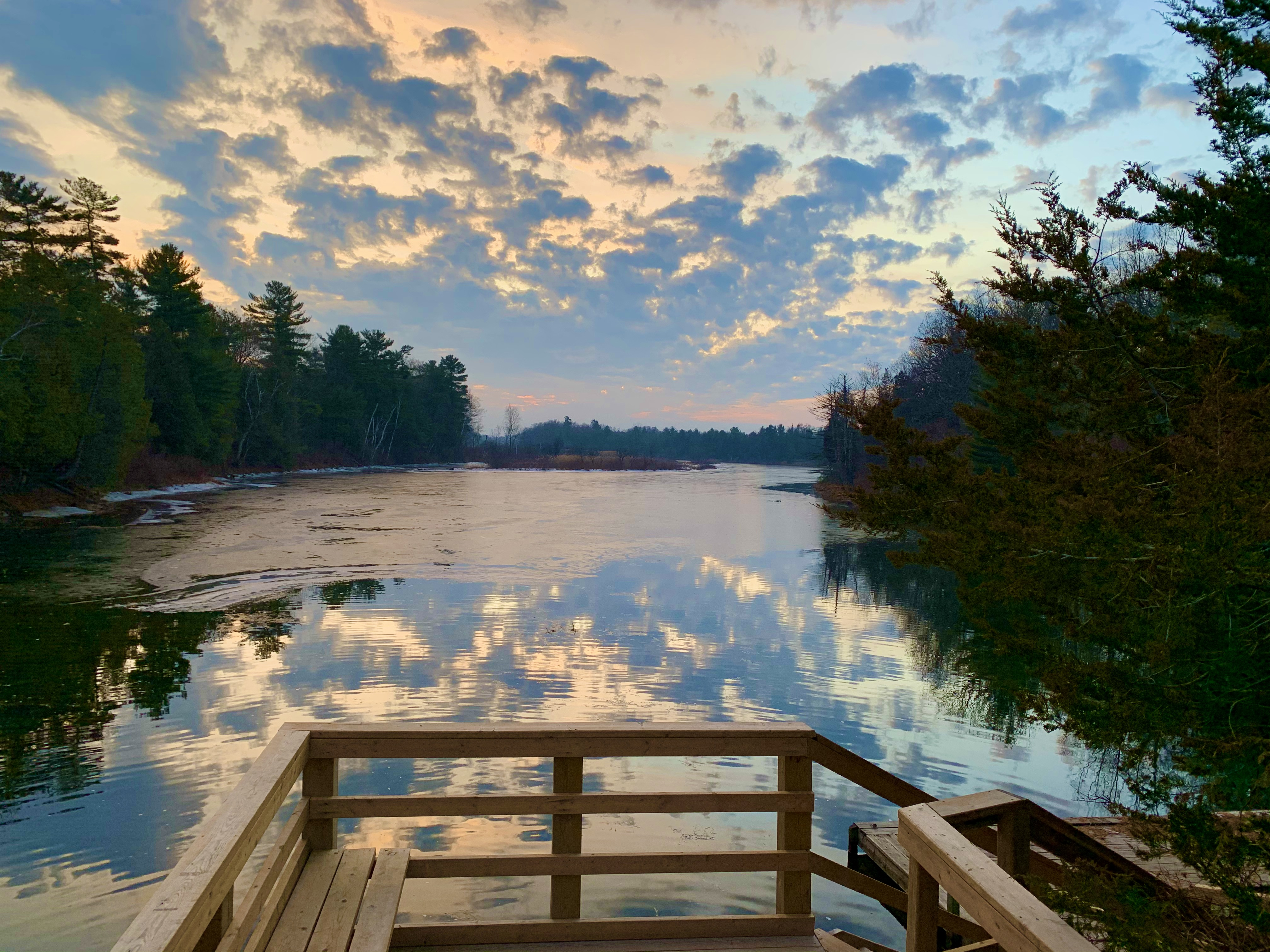 dramatic clouds reflected in still water by a dock