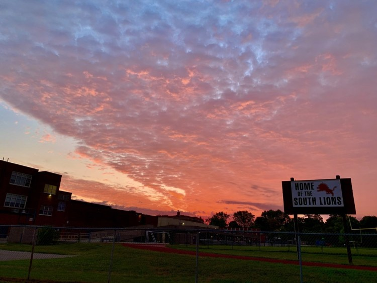 vivid sunrise-coloured sky with silhouette of playing field scoreboard
