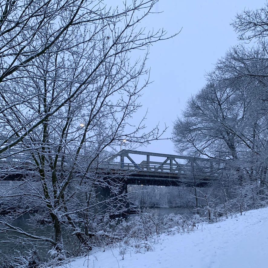 winter scene with a snow-covered bridge and river