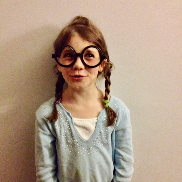 same young girl wearing the same glasses and a funny smirk