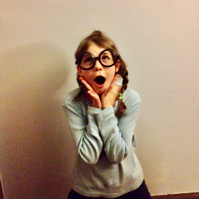 same young girl wearing same funny glasses and making a fake shocked face