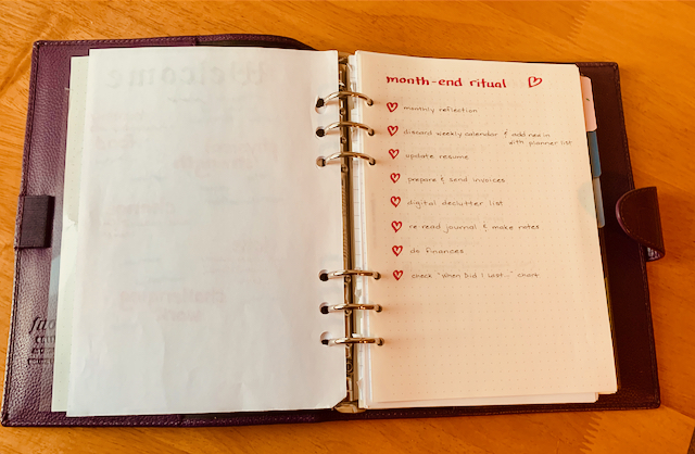 Medium size 6-ring binder with a page showing with a list of items in a month-end ritual: monthly reflection, update resume, digital declutter list, do finances, prepare and send invoices, and update resume.