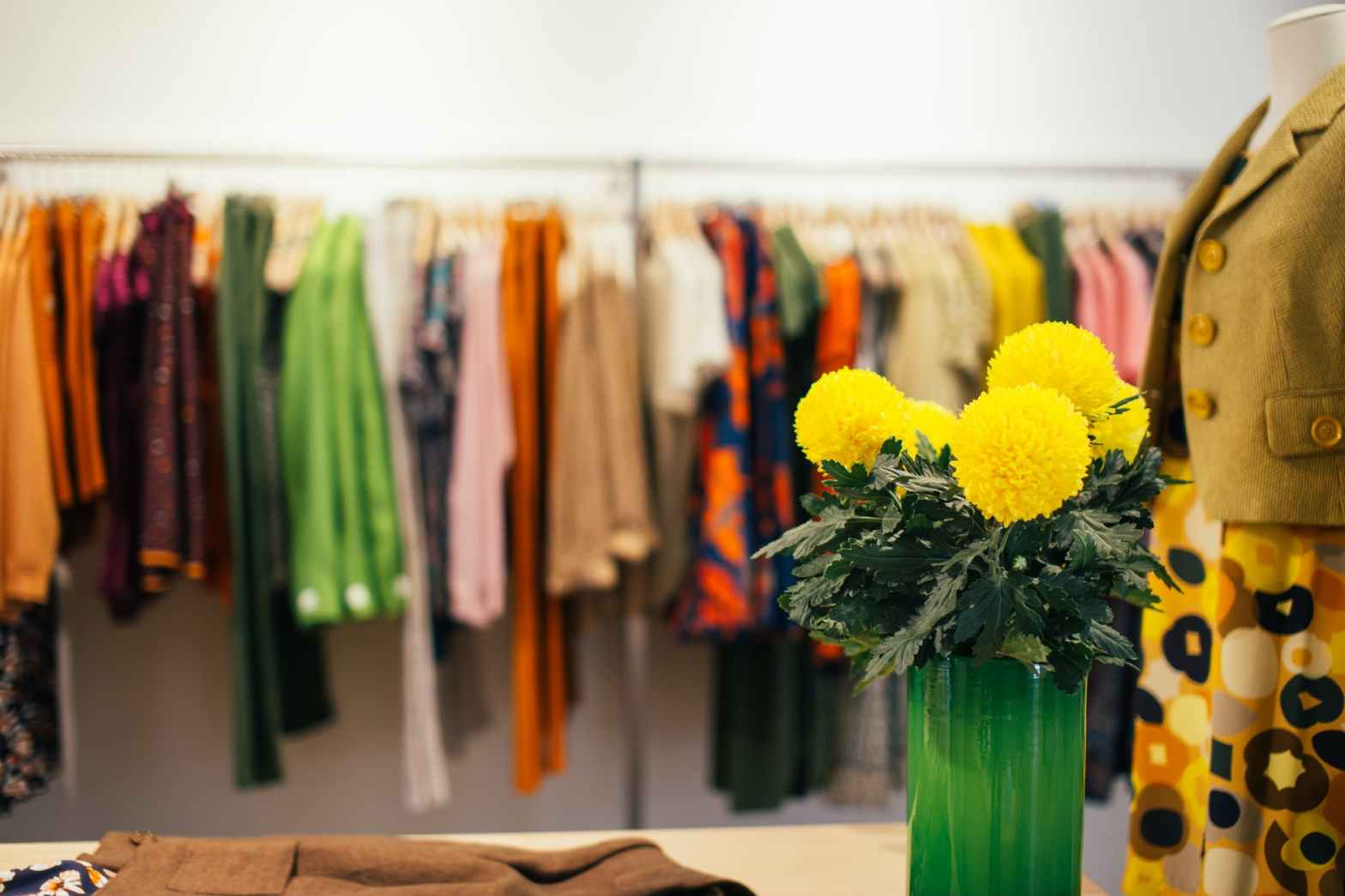 assorted colorful clothes hanging on rack in store