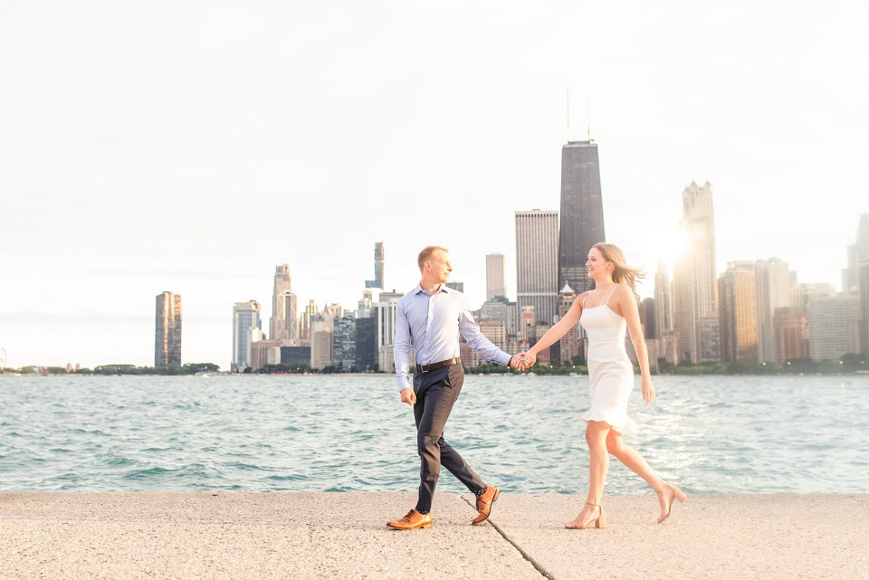 Beautiful couple walking at North Avenue Beach with Chicago Skyline engagement photos by Karen Shoufler Photography