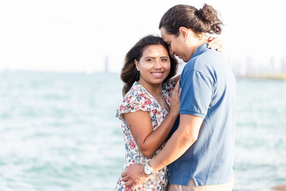 Sweet, romantic walking photo of engagement session at Montrose Beach with Chicago Skyline by Karen Shoufler Photography